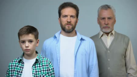 parentes : Serious adult men standing behind sad boy, past and future, unhappy childhood