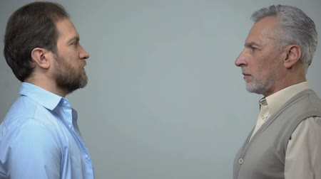 poll : Senior and middle-aged men staring each other, male health, present and future Stock Footage