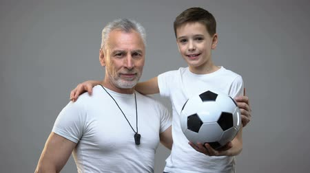 motivováni : Senior football coach smiling hugging teen boy, active healthy lifestyle, sports