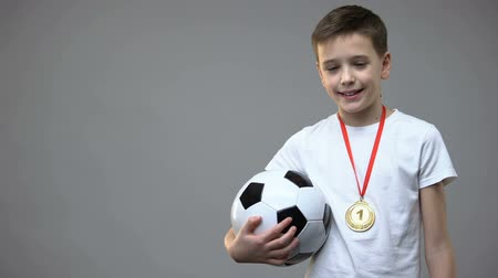sucesso : Happy boy smiling with winner medal on chest, holding soccer ball, champion