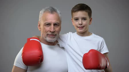 motivados : Active senior male and boy in boxing gloves looking to camera, healthy lifestyle
