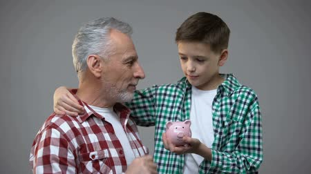 alfabetização : Elderly man putting coin into little boy piggy bank, savings for future, banking
