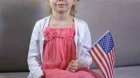 гордый : Cute female child with american flag in hand sitting sofa, independence day