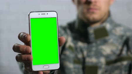 chránit : Male in camouflage showing smartphone with green screen closeup, application