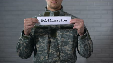 歩兵 : Mobilization word written on sign in male soldier hands, preparing for war