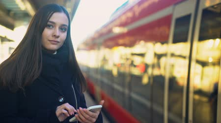 прибытие : Female typing on phone near train, quick mobile payment for tickets technologies