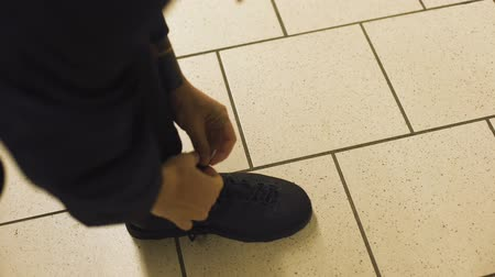 tying : Male tying shoelaces on boots standing on tile floor, comfortable footwear, POV