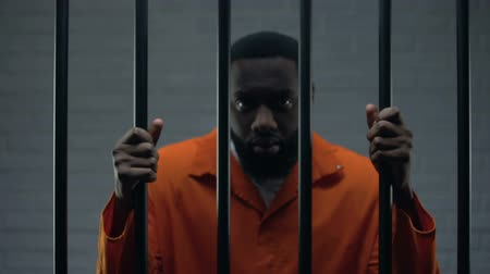 imprison : African-american male prisoner holding bars and looking to camera, imprisonment Stock Footage