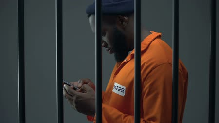 заключенный : Afro-american prisoner using phone in cell, corruption in prisons, prohibition