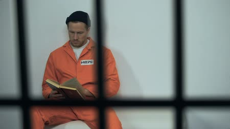hapsedilme : Caucasian prisoner reading bible in cell, convicted sinner turning to religion