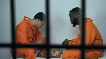 vazba : Caucasian and afro-american jail inmates playing chess in cell, hobby in prison