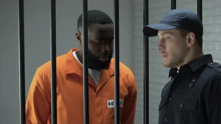 dose : Prison guard giving afro-american imprisoned male dose of drugs illegal activity Stock Footage