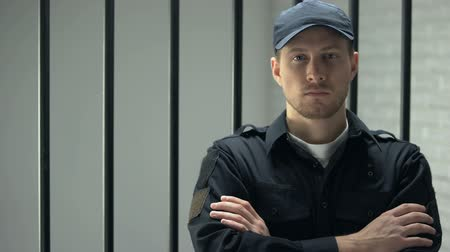 охранять : Confident prison security guard looking to camera standing near cell, profession