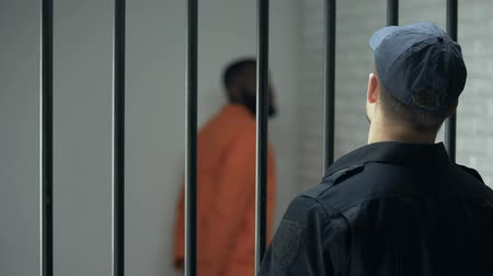 охранять : Warden looking at dangerous criminal walking in cell, life sentence, prison Стоковые видеозаписи