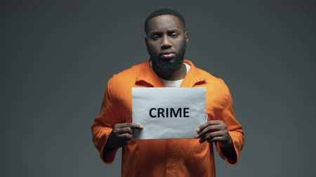 гангстер : African-american prisoner holding Crime sign, looking to camera, awareness Стоковые видеозаписи