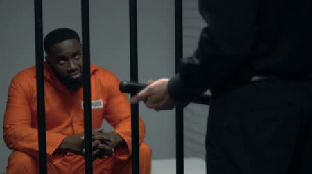 охранять : Jail guard with baton looking at afro-american prisoner in cell, harassment