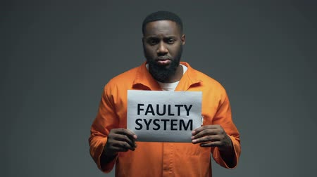 hapsedilme : African-american male prisoner holding Faulty system sign in cell, human rights Stok Video