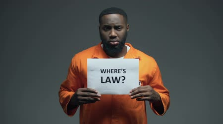 accused : Afro-american prisoner holding Where is law sign in cell, wrongly accused person Stock Footage