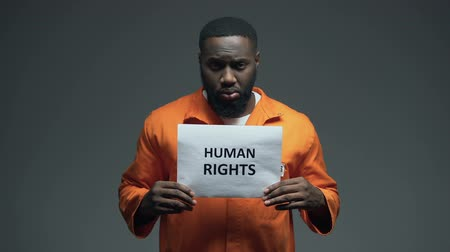 haklar : Afro-american prisoner holding Human rights sign, ill treatment, awareness