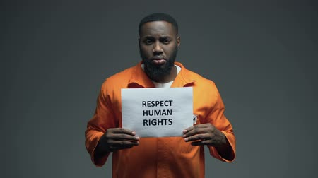 accused : Black male prisoner holding Respect human rights sign in cell, sexual harassment