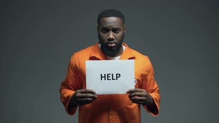 accused : African-american male prisoner holding Help sign, asking for justice, abuse Stock Footage