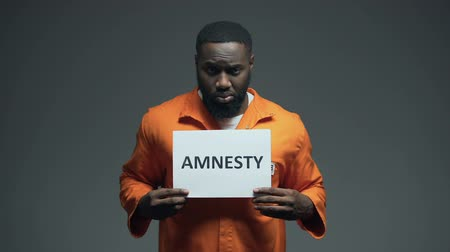 penas : Afro-american prisoner holding Amnesty sign, asking for help, human rights