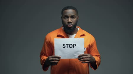 hostility : Afro-american prisoner holding Stop sign, racial discrimination, persecution