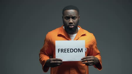 ethic : Black imprisoned male holding Freedom sign in cell, asking for help human rights