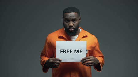 ethic : African-american prisoner holding Free me sign in cell, innocent asking for help Stock Footage