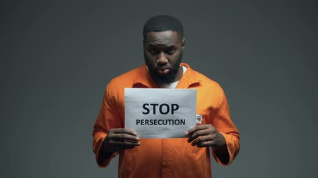 hostility : Afro-american prisoner holding Stop persecution sign, racial discrimination