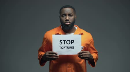 perseguição : Black male prisoner holding Stop tortures sign, ill treatment abuse of force