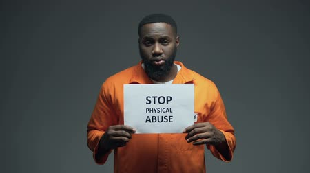 yaşama gücü : Black male prisoner holding Stop physical abuse sign in cell, sexual harassment