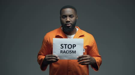 culpado : Black prisoner holding Stop racism sign, psychological abuse, ill treatment