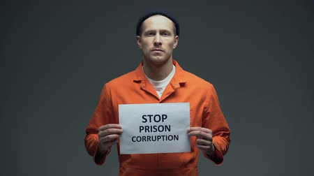 hapsedilme : Caucasian imprisoned male holding Stop prison corruption sign, faulty system Stok Video