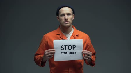 mistreatment : European prisoner holding Stop tortures sign, physical abuse in cell, harassment