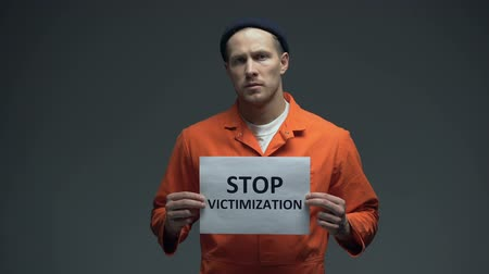 culpado : Caucasian prisoner holding Stop victimization sign violent treatment in jail