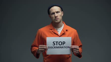perseguição : Caucasian imprisoned man holding Stop discrimination sign, racial prejudice