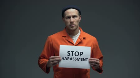 penas : European imprisoned male holding Stop harassment sign in cell, asking for help Stock Footage