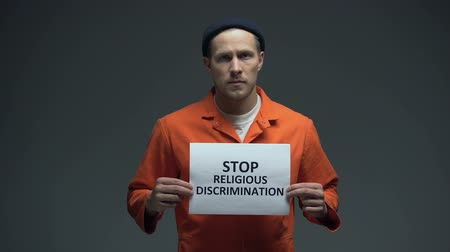 perseguição : European male prisoner holding Stop religious discrimination sign, pressure
