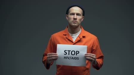 hapsedilme : Imprisoned man holding Stop HIV AIDS sign in cell, sexually transmitted disease