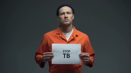 transmitted : Male prisoner holding Stop TB sign, healthcare in prison, life conditions