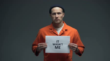 nevinný : European imprisoned man holding It was not me sign, wrongly convicted person