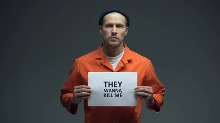 they : Caucasian male prisoner holding They wanna kill me sign, calling for help