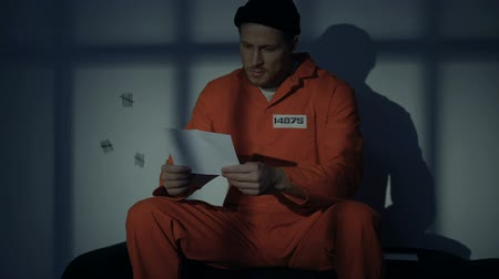 prisioneiro : Prisoner receiving letter from family, feeling homesick, application for pardon Stock Footage