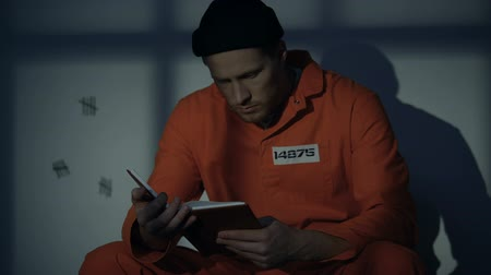 mevcut : Imprisoned male reading book in jail cell, available hobby, self-education