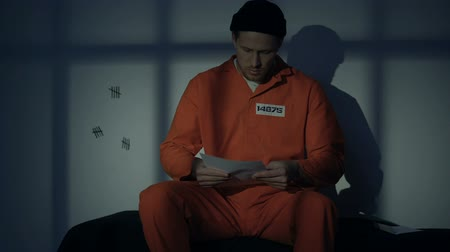 заключенный : Caucasian male prisoner writing letter, missing family, composing mercy petition