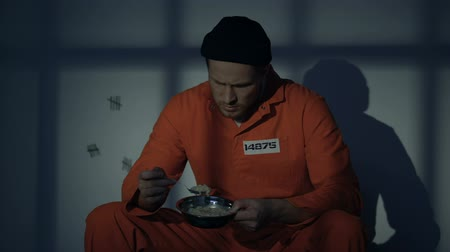 наказание : Displeased prisoner looking with disgust at unappetizing food, poor conditions Стоковые видеозаписи