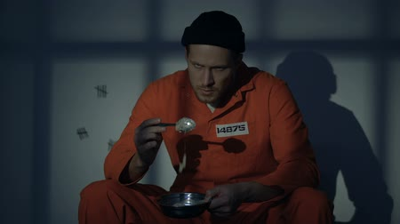 заключенный : Upset imprisoned man holding plate with disgusting food, human rights violation
