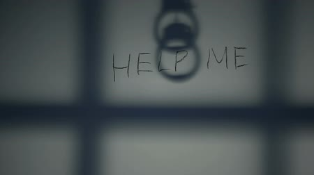 mistreatment : Help me phrase written on prison wall, handcuffs and bars shadow, despair