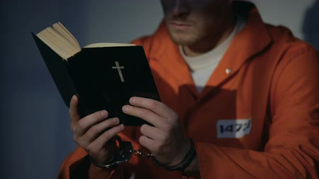 vazba : Imprisoned man in handcuffs reading bible, feeling guilty and praying for soul